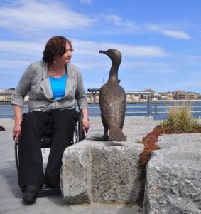 Woman in wheelchair staring into the eyes of a bronze duck sculpture with harbor in background.