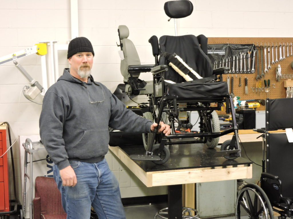 Man standing at workbench with wheelchairs and tools.