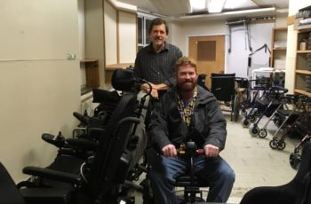 Two smiling men in a large room with mobility equipment, one is seated on a scooter.