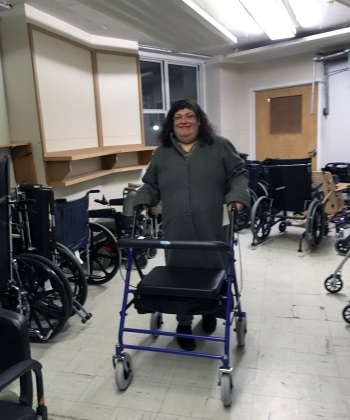 Smiling woman with rollator in a room full of DME.