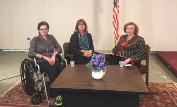 Three women seated, one in a wheelchair, around a coffee table.