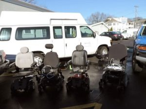REquipment's delivery van with four power wheelchairs.