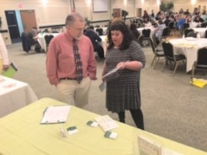 A man and woman talking at a vendor table in a conference space.