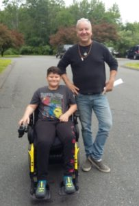 Smiling boy seated in power wheelchair next to standing smiling man.