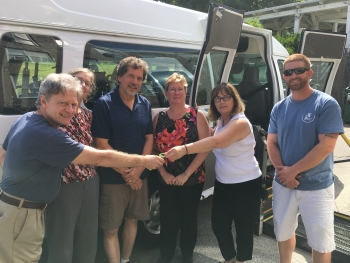 3 men and 3 women standing in front of a van. A woman passes a key to a man.