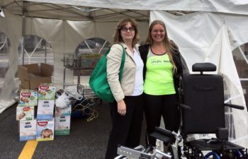 Two women standing and smiling in front of a tent with wheelchairs and boxes of disposable adult diapers.