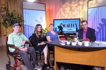 Four adults on the TV set of Soapbox seated. One man is in a transport wheelchair, another is behind a desk. Two women are seated between them.