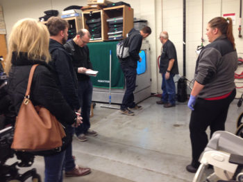 A group of adults studying the HUBSCRUB in a warehouse space.