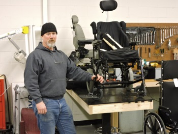 A man stands next to a workbench with a wheelchair and tools