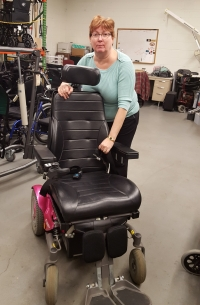 A woman standing behind and leaning over a power wheelchair, looking at the camera.