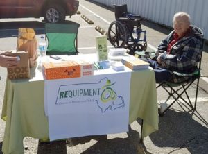 An older woman seated outside in a parking lot next to a REquipment donation day table with banner and brochures and donuts. A wheelchair in the background.