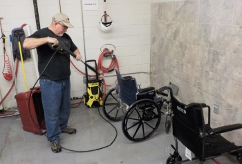 A man using power wash equipment on a wheelchair.