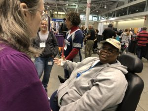 A smiling African-American woman in a large power chair in a busy expo hall.