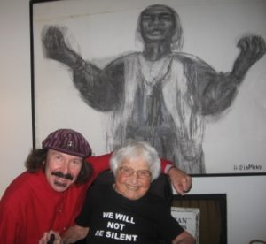 An elderly woman seated in a power chair in front of a large portrait of Sojourner Truth. A man is next to her with he arm around her. She wears a t shirt that reads We will not be silent.