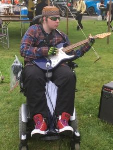 A young man playing an electric guitar seated in a power wheelchair. He's wearing sunglasses and a headset and red hi-top sneakers.