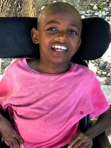 A Haitian boy seated in a wheelchair with head support smiling.