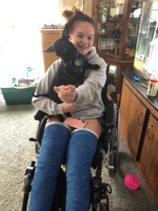 Girl in wheelchair smiling and pointing holding small dog and wearing two above-knee casts.