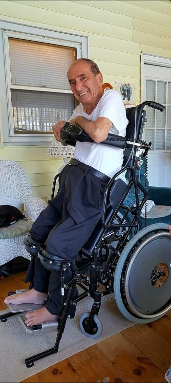 Man smiling upright in a standing wheelchair.