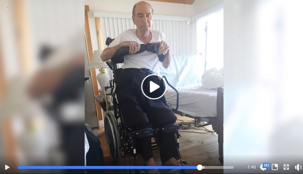 Video screen shot of man in a standing wheelchair next to his hospital bed.