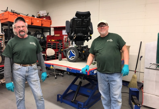 Two men smiling in front of a workbench with a power wheelchair wearing REquipment t-shirts.