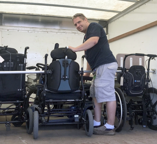 A smiling man loading mobility equipment into a storage unit.