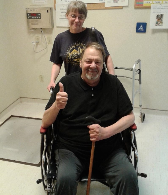 A man seated in wheelchair gives a thumbs up. His wife stands behind him smiling. They are in a hospital hallway. He holds a cane.