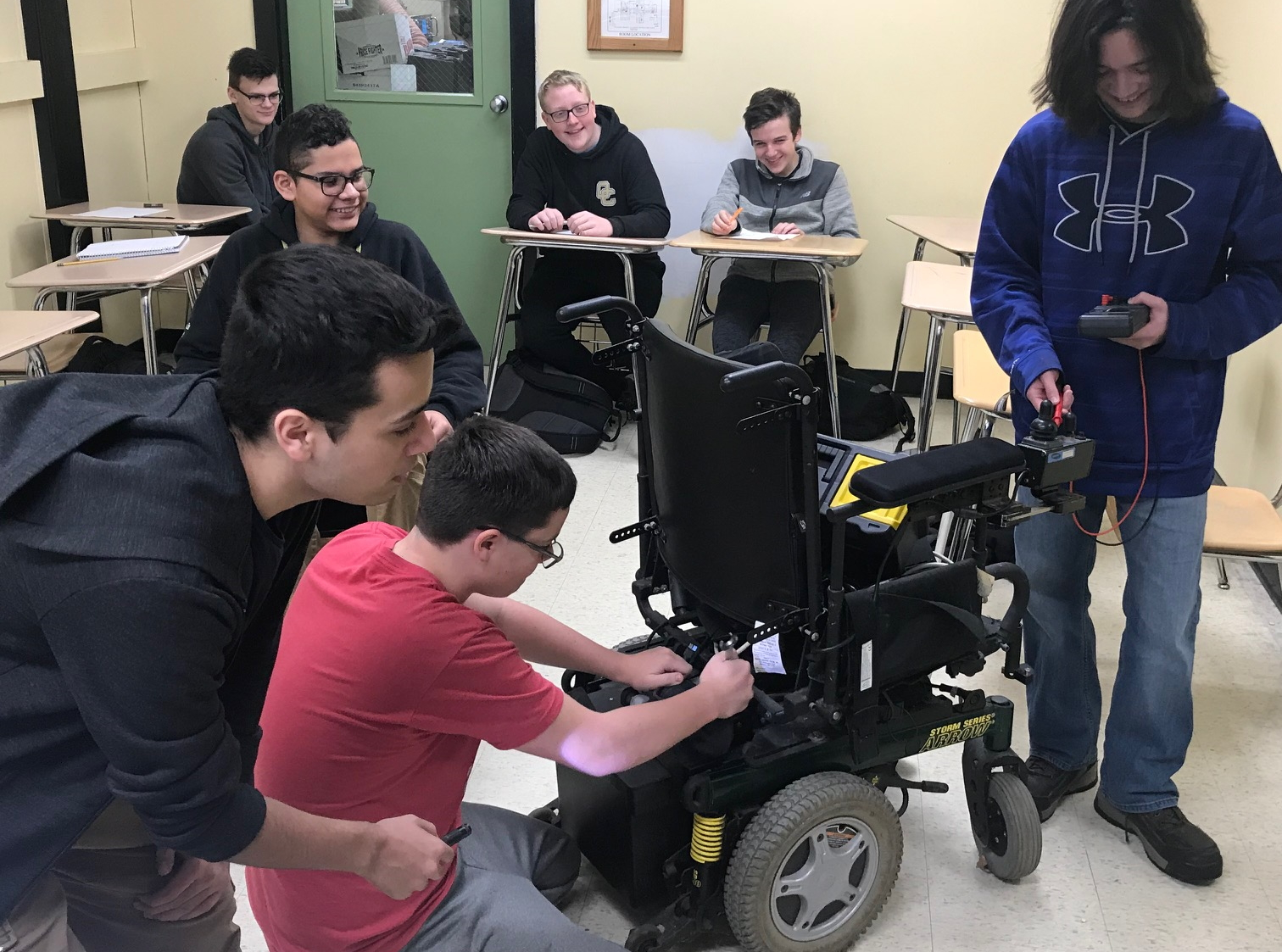 Smiling high school-aged boys repair a power wheelchair.