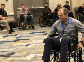 Men operating manual wheelchairs in a conference hall.