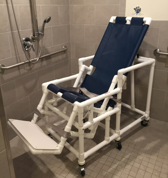 A showerchair with foot support and in a semi-reclined position.