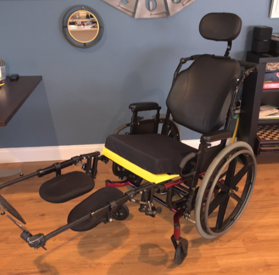 A manual wheelchair with head support and leg supports extended.