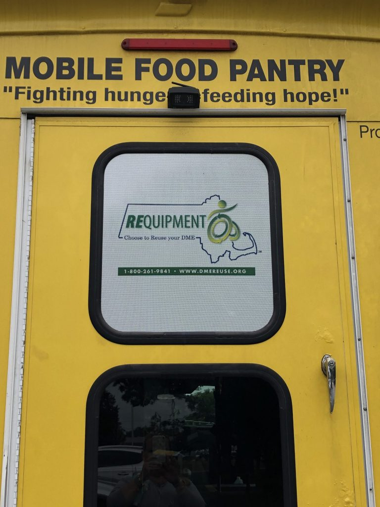 Back of the Mobile Food Pantry bus shows slogan Fighting Hunger - Feeding Hope and in a window is the REquipment logo.