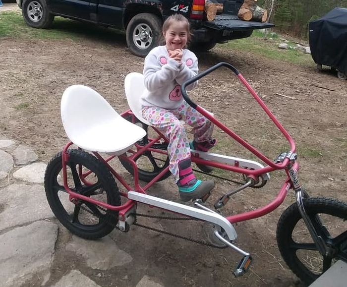 A little girl smiling on a two-seater trike.